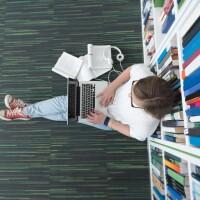 Girl sitting on floor in library