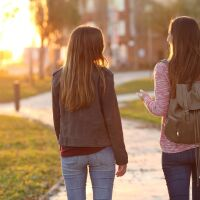 Two female students talking and walking away down a sidewalk