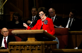 Sister Oaks speaking at a pulpit.