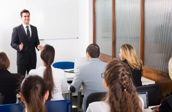 young man presenting in front of a classroom of students