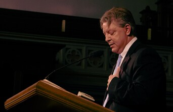 Travis Blackwelder speaking at a pulpit.