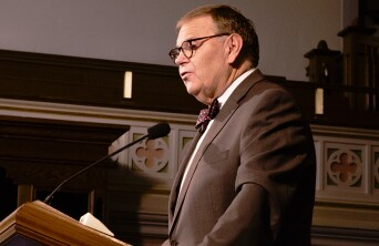 Lee Tom Perry speaking at a pulpit.
