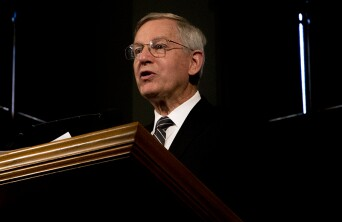 John W Welch speaking at a pulpit.
