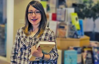 Alejandra Martinez holding a book and smiling.