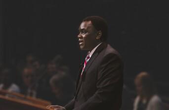 Elder Edward Dube speaking at a pulpit.