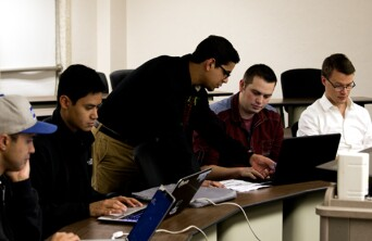 Group of students studying on computers together.