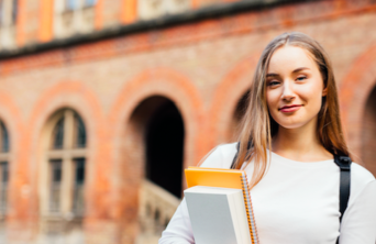 female student smiling in front of campus