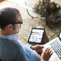 man with laptop on his lap and tablet to his side