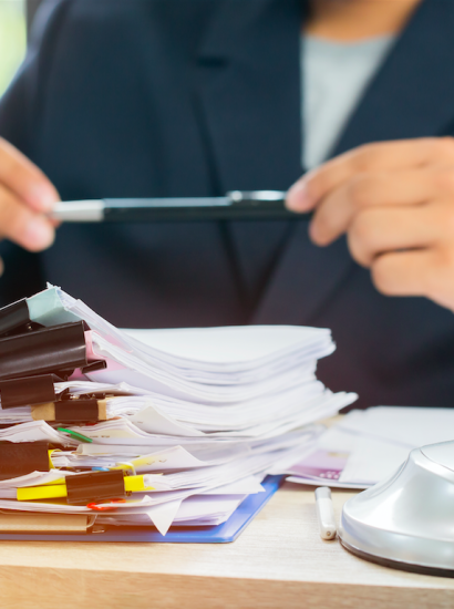 paralegal at desk reviewing stack of records