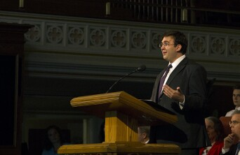 Adrian Juchau speaking at a pulpit.
