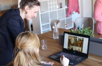 two girls at a computer smiling