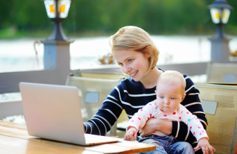 single mother doing homework with baby on her lap