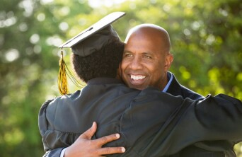 Male parent hugging his son at graduation.