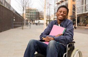 Smiling African American young man in wheelchair holding folders