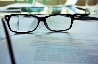 Close up of eye-glasses placed on some papers on a desk