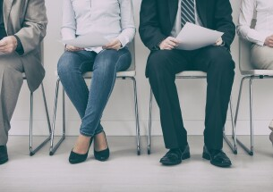 job applicants waiting for interview with resumes