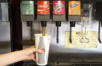 Someone filling up their cup with coke from BC Cafe soda fountain