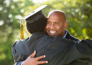 Male parent hugging his son at graduation.