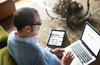 male with laptop on lap and tablet to his side