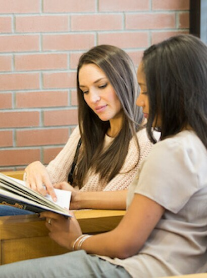 Two female students read a book together