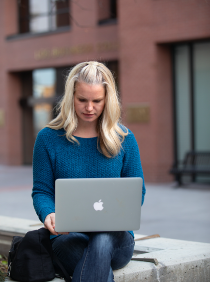 female student on laptop on campus