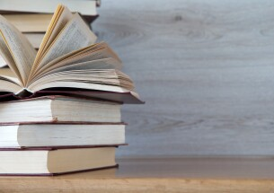 Stack of books on the left of a table with a wooden background