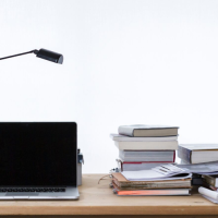 Desk full of books with a computer and a lamp
