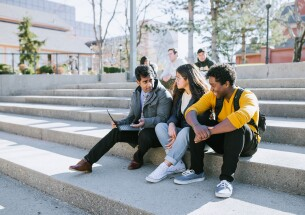 Students sitting outside by computer smiling