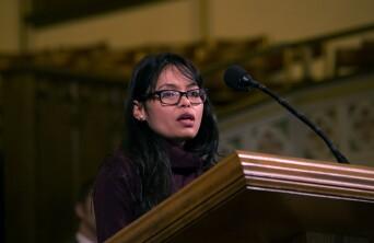 Devi Paryiar speaking at a pulpit.