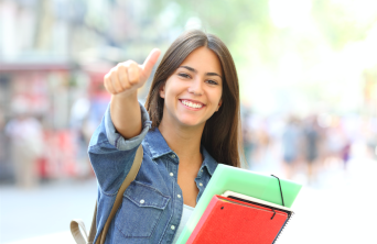 smiling female student giving a thumbs up