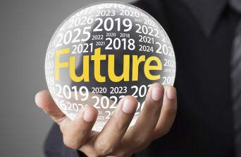 """Image of a person holding a globe that has the text """"Future"""" in the middle with bunch of future year text surrounding it."""