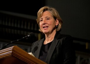 Natalie Gochnour speaking at a pulpit.